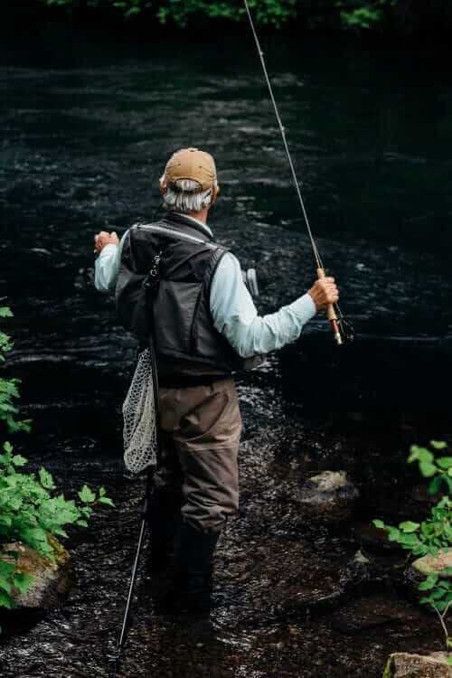 man fishing on stream at daytime