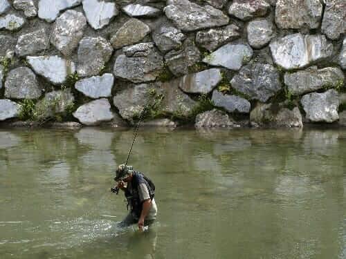 man holding fishing rod on lake