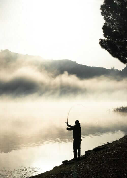 person standing on shore while fishing