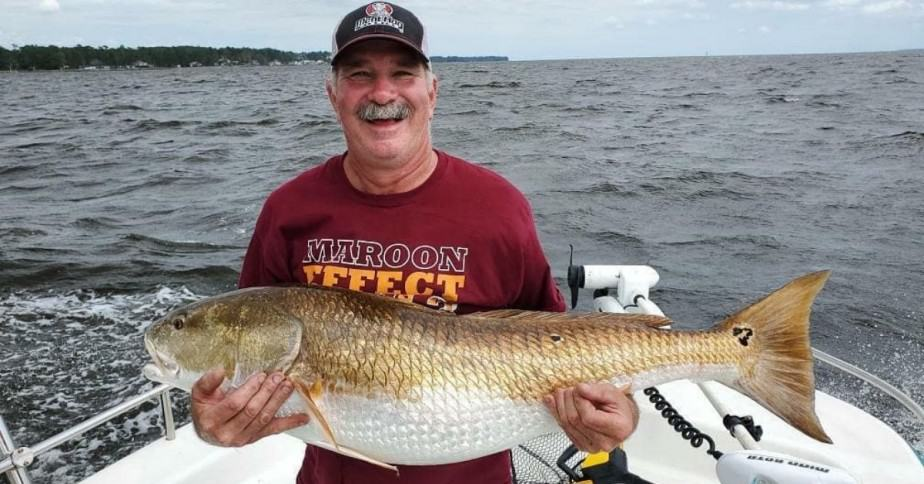 Fisherman holding red drum
